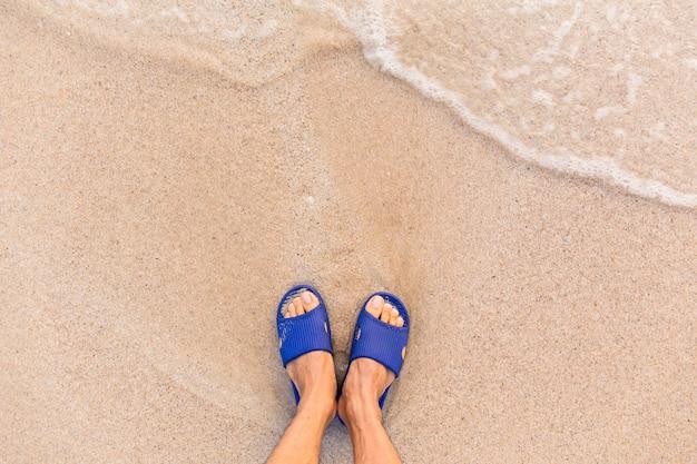 Jambes d'hommes debout à la plage. concept de loisirs et de vacances en mer.