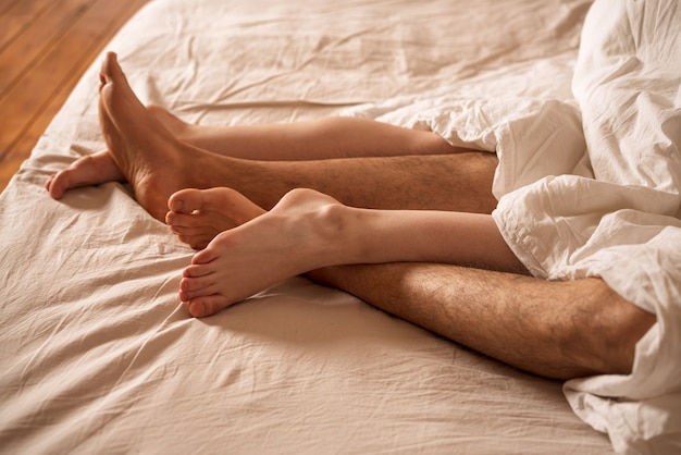 Les jambes des hommes et des femmes dépassent de sous la couverture.