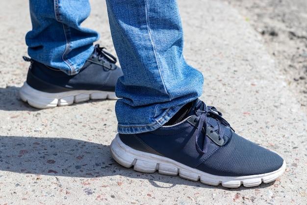 Les jambes des hommes en jean bleu et des baskets à semelles blanches se tiennent sur le trottoir par une journée ensoleillée