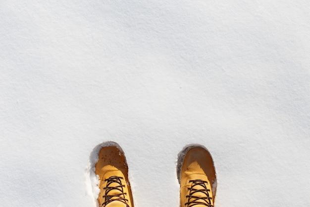 Jambes humaines avec des bottes en cuir jaune debout dans la neige