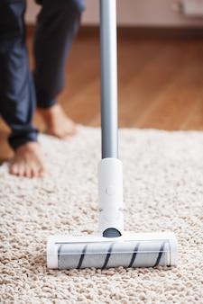Des jambes humaines et une brosse turbo blanche d'un aspirateur sans fil nettoient le tapis de la maison