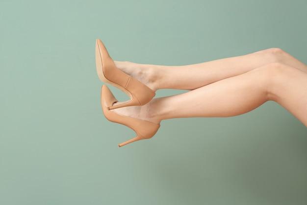 Jambes de jeune femme dans des chaussures élégantes sur la couleur