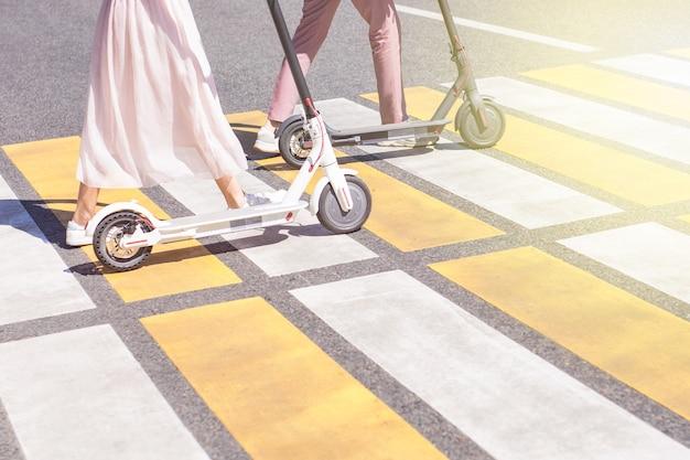 Jambes de jeune femme et jambes d'homme marchant avec des scooters sur la route croisée avec des rayures jaunes et blanches