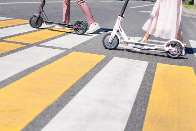 Jambes de jeune femme et jambes d'homme marchant avec des scooters sur la route transversale