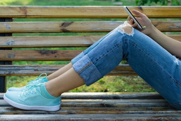 Jambes d'une jeune femme en jeans sur un banc dans le parc