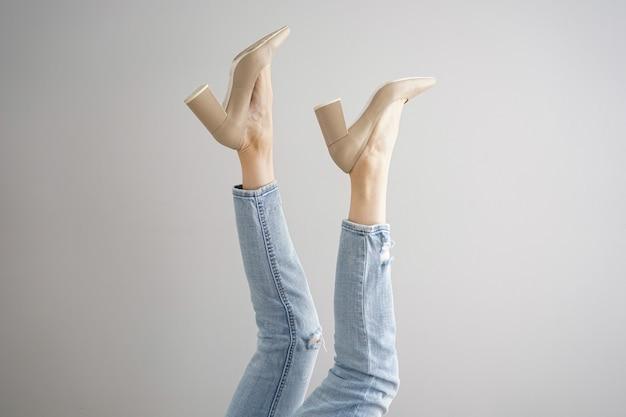 Jambes d'une jeune femme en jeans et chaussures sur fond gris.