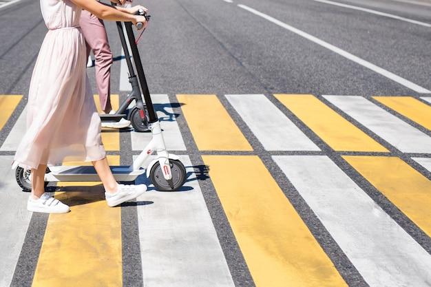Jambes de jeune femme en jupe rose clair et jambes d'homme marchant avec des scooters sur la route du carrefour zébré