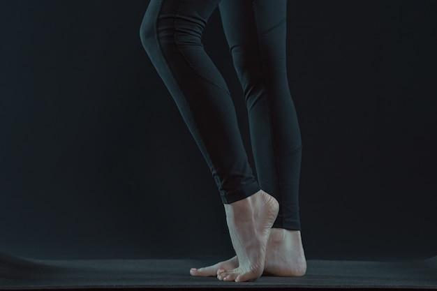Jambes de jeune femme pratiquant le yoga sur tapis de yoga