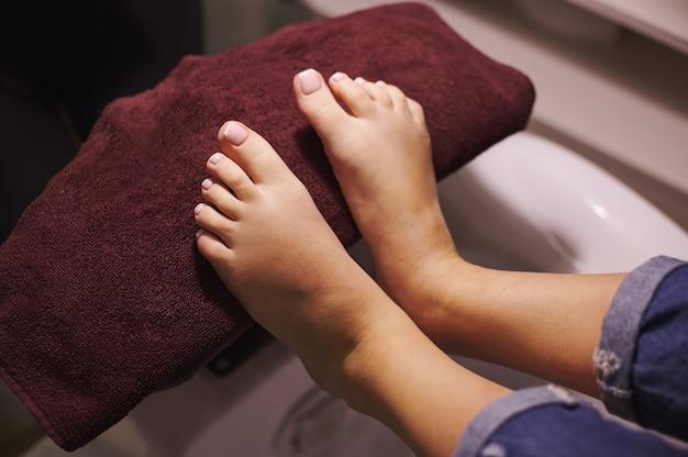 Les jambes de la jeune femme sur une serviette après une pédicure professionnelle faite par le maître en salon de beauté. concept de soins du corps