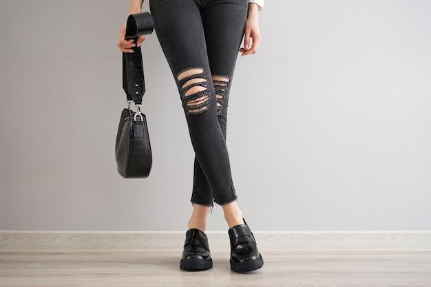 Jambes d'une jeune fille en jean noir avec un sac et des chaussures sur fond gris.