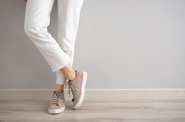 Jambes d'une jeune fille en jeans et baskets sur fond gris, place pour le texte.