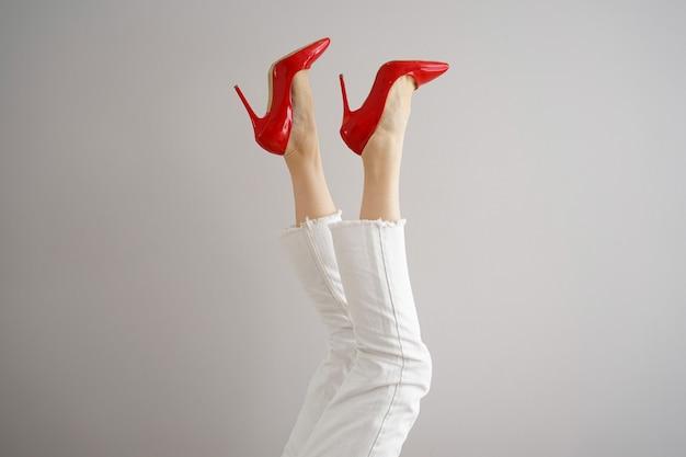 Jambes d'une jeune fille en jeans blancs et chaussures rouges sur fond gris.