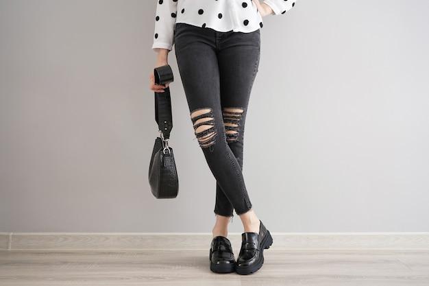 Jambes d'une jeune fille en jeans avec un sac et des chaussures sur fond gris.
