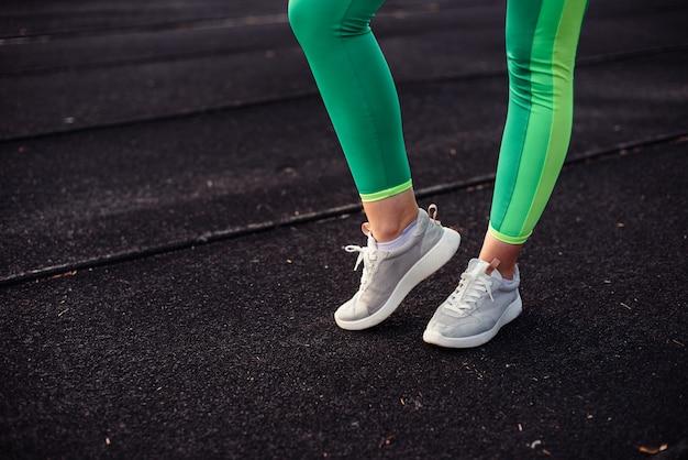 Jambes d'une jeune fille en leggings vert clair lors d'une session de formation sur un stade, dans la rue. les jambes se réchauffent