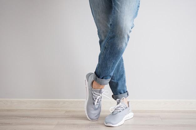 Jambes d'un jeune homme en jeans et baskets sur un mur gris.