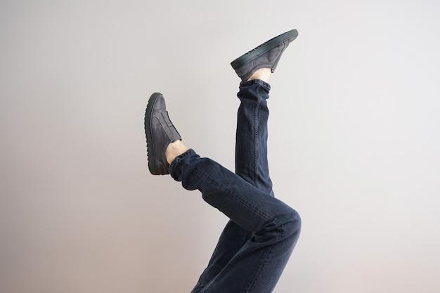 Jambes d'un jeune homme en jeans et chaussures sur fond gris.