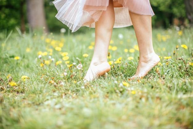 Jambes de jeunes femmes aux pieds nus, vêtue d'une robe rose, debout sur une jambe sur l'herbe verte à fleurs jaunes, gros plan