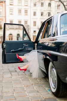 Jambes de jolie femme mariée en rouge haute guérit assis dans une voiture rétro noire, vieux bâtiments de la ville en arrière-plan.
