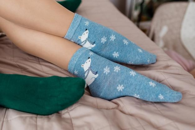 Jambes avec de jolies chaussettes bleues avec des ours blancs et des chaussettes vertes sur le lit