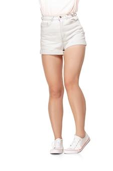 Jambes longues jolie femme isolés sur mur blanc avec fond. prêt pour votre conception. concept sportif et en forme de figure, de mode et de beauté.