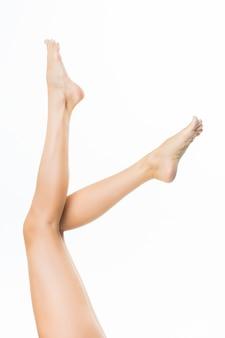 Jambes longues jolie femme isolés sur mur blanc