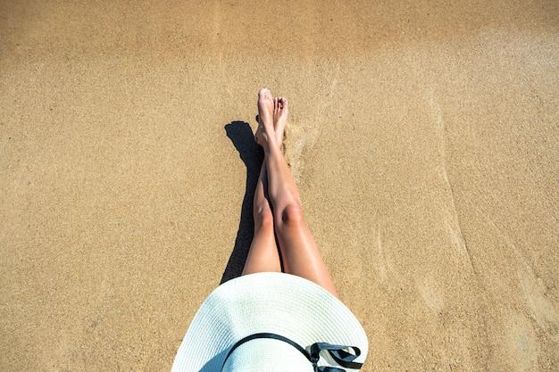 Jambes longues et minces de jeune femme se détendre couchée et bronzer sur la plage tropicale de sable sous le soleil chaud en été.