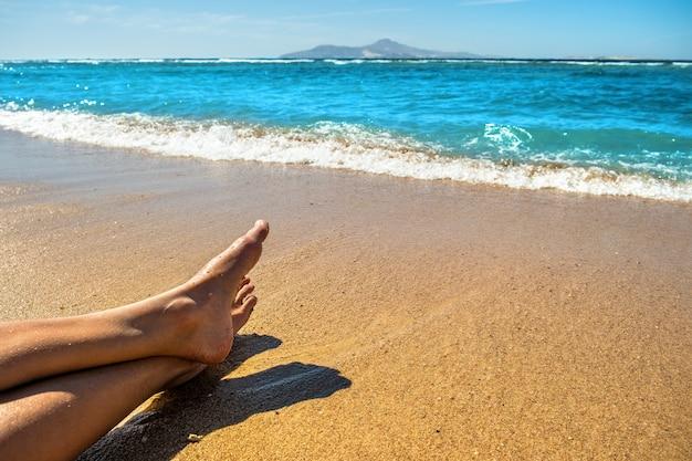 Jambes longues et minces de jeune femme se faire bronzer sur la plage tropicale