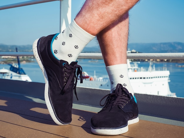 Jambes mâles en chaussettes dans le contexte des vagues de la mer. fermer. concept de vacances et de voyage