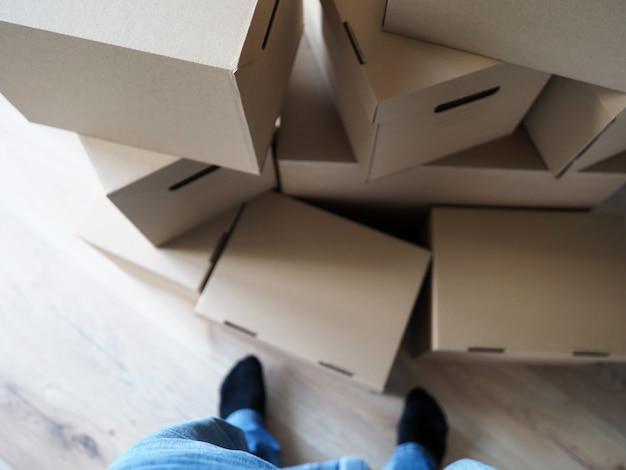 Jambes mâles debout près d'un énorme tas de boîtes en carton