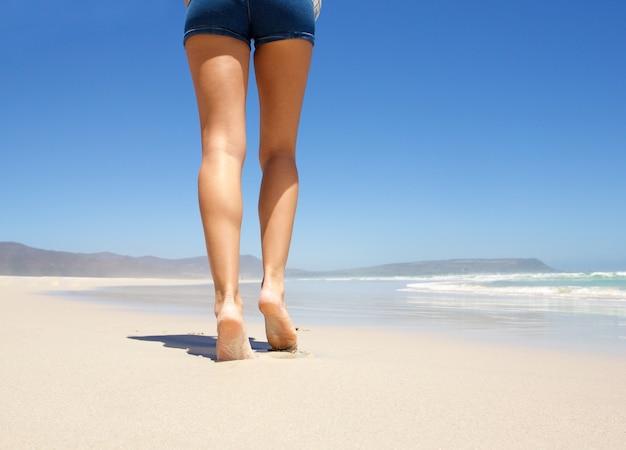 Jambes marchant pieds nus sur la plage