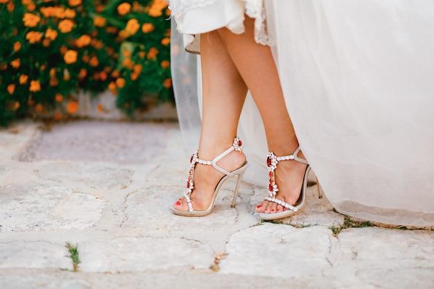 Les jambes des mariées dans des sandales élégantes avec des cristaux avec des talons hauts se détachent sous la robe de mariée