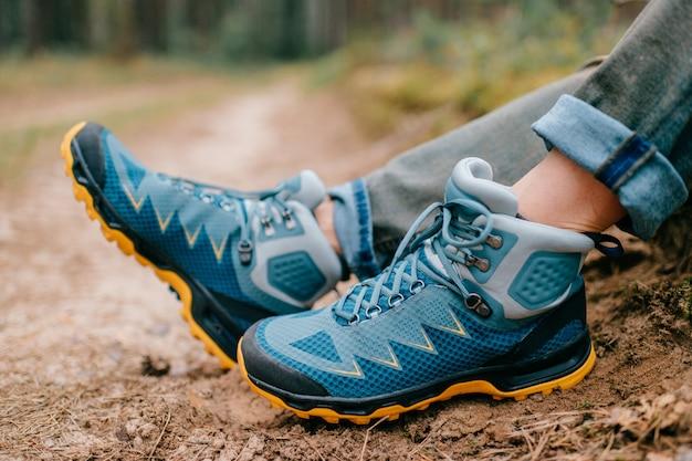 Jambes masculines portant des chaussures de randonnée sportive.