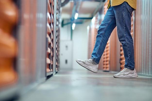 Jambes mesurant en marches la largeur du couloir entre les garages