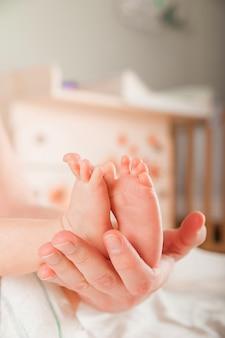 Jambes d'un nouveau-né en gros plan de mains. pieds de bébé et espace copie. soins aux nourrissons et coliques