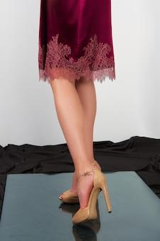 Jambes nues de femmes dans des chaussures à talons hauts.