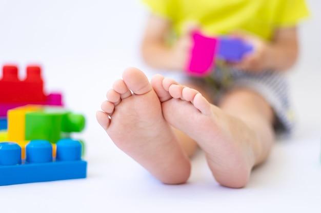 Les jambes d'un petit garçon sur fond blanc, l'enfant joue avec un constructeur, isolent