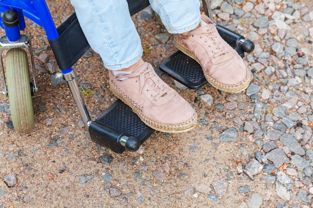 Jambes pieds handicap femme en roue de fauteuil roulant sur la route dans le parc de l'hôpital en attente de services aux patients. fille paralysée méconnaissable dans une chaise invalide pour les personnes handicapées à l'extérieur. concept de réadaptation.