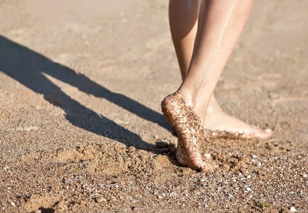 Jambes pieds nus de la fille sur la plage de sable