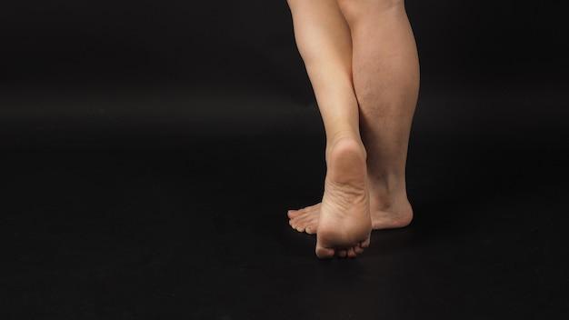 Les jambes et les pieds nus masculins asiatiques sont isolés sur fond noir