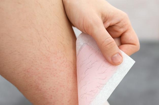 Jambes poilues. femme utilisant une bande de cire d'abeille pour se raser la jambe. procédure d'épilation à la cire, gros plan. concept d'épilation.