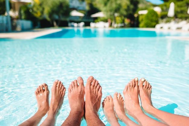 Jambes de quatre personnes au bord de la piscine