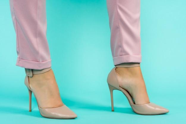 Jambes sexy en chaussures à talons hauts marron sur fond bleu.