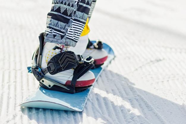 Jambes de snowboarder en gros plan sur le snowboard sur la neige fraîche de velours