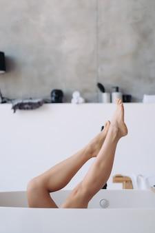 Jambes sortant d'une baignoire.