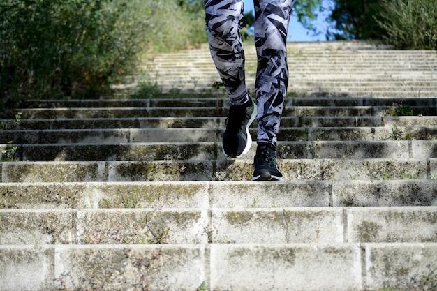 Les jambes de la sportive en descendant les escaliers dans un parc. concept en cours d'exécution.