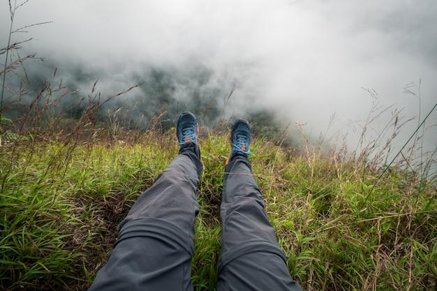 Jambes de voyageur assis sur une haute montagne. concept de liberté