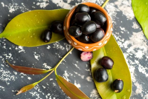 Jambolan prune ou jambul ou jamun fruit, prune de java (syzygium cumini) avec feuille sur pierre