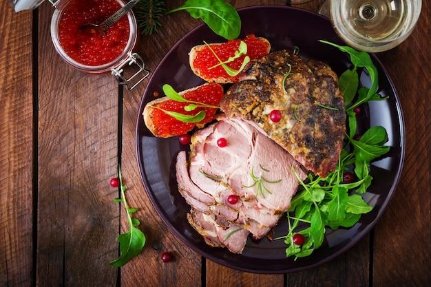 Jambon cuit au four et caviar rouge, servi sur la vieille table en bois.