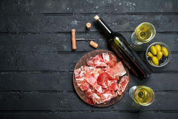 Jambon espagnol à bord avec du vin blanc sur table rustique.