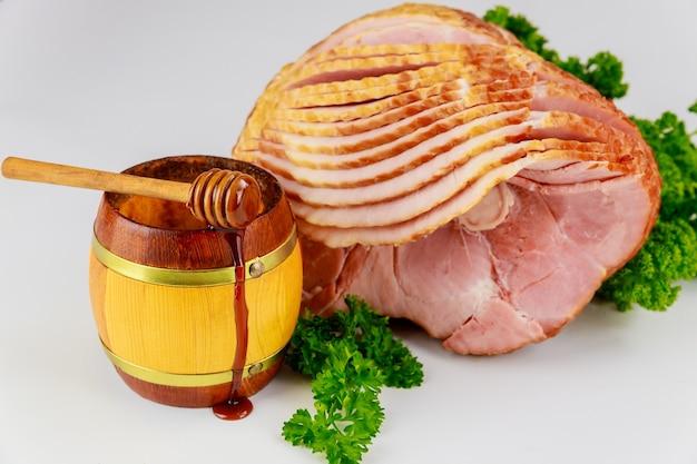 Jambon fumé à l'hickory en tranches avec du miel dans un bocal en bois.